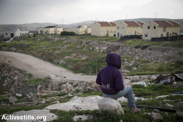 A Palestinian boy looks on at the Israeli settlement of Carmel from the Bedouin village of Umm Al-Khair, in the South Hebron Hills, West Bank, February 23, 2016. (Oren Ziv/Activestills.org)