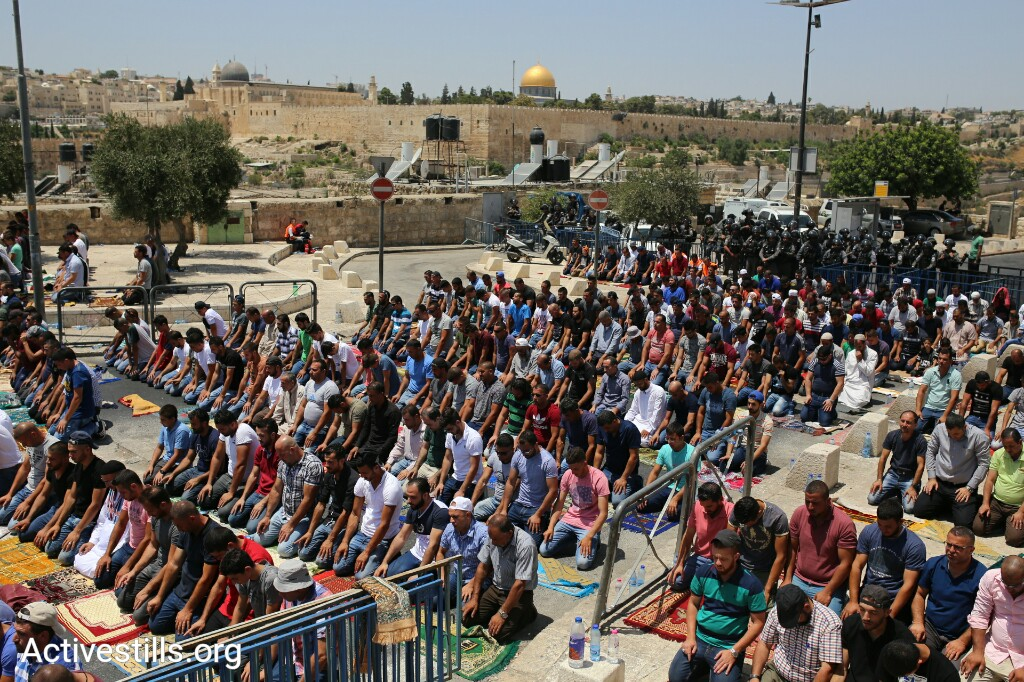 Hundreds of Palestinians pray in the East Jerusalem neighborhood of Ras al-Amud, outside the Old City, July 28, 2017. (Activestills.org)