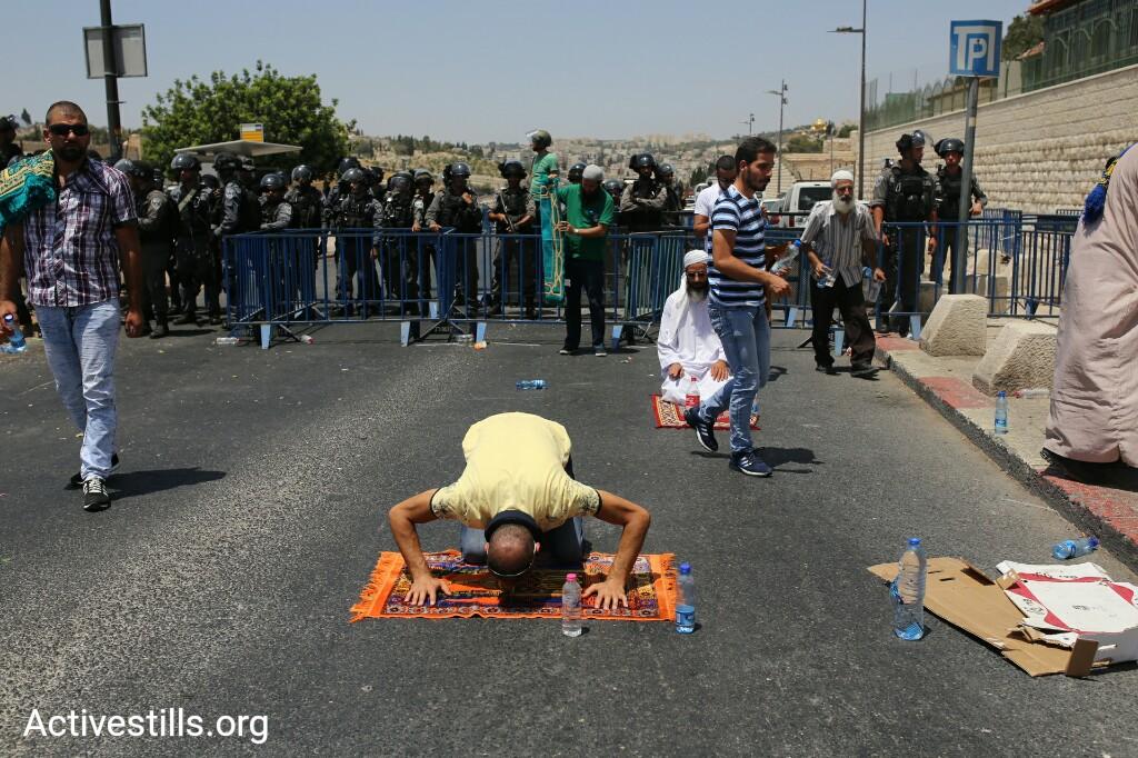 A Palestinian worshipper prays in Ras al-Amoud, East Jerusalem, July 28, 2017. (Activestills.org)