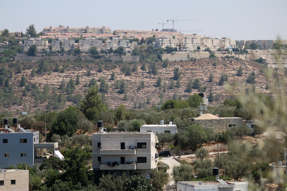 The settlement of Gilo seen behind Walajeh, August 18, 2017. (Ahmed Al-Bazz/Activestills.org)