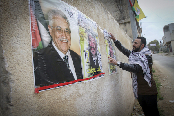 A Palestinian man hangs posters of Mahmoud Abbas and Yasser Arafat in the West Bank city of Nablus, March 14, 2017. (Nasser Ishtayeh/Flash90)
