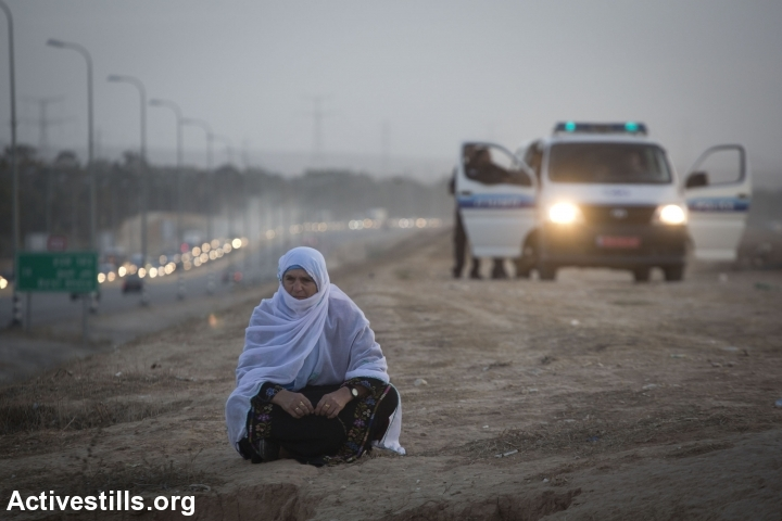 A Bedouin woman from the unrecognized village of Al-Araqib sits in front of an Israeli police van. Israel has demolished al-Araqib over 100 times. (Illustrative photo by Oren Ziv/Activestills.org)
