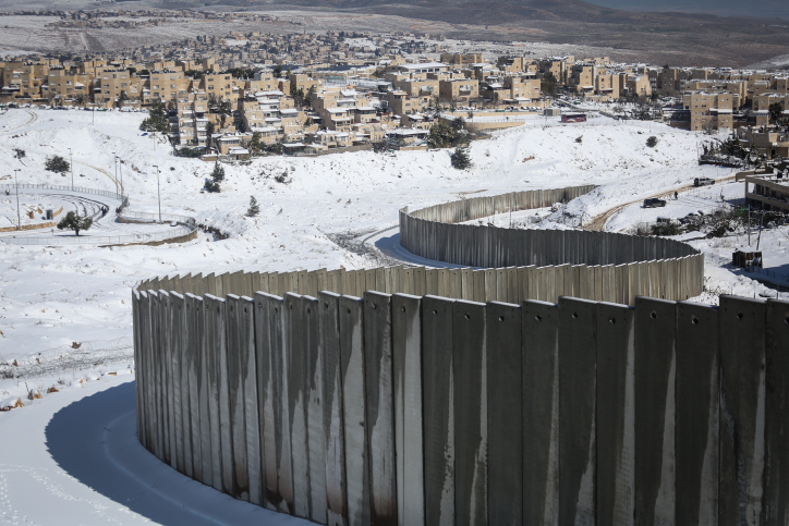 The separation wall surrounds Shuafat refugee camp in East Jerusalem, seen on a snowy winter morning,February 20, 2015. (Hadas Parush/Flash90)