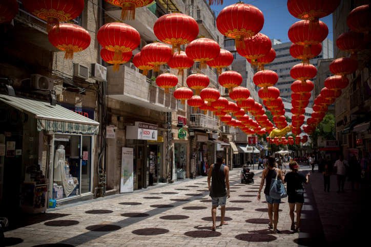 Pepole walk under rows of hanging Chinese lamps used to decorate a street in downtown Jerusalem, July 26, 2016. (Yonatan Sindel/Flash90)