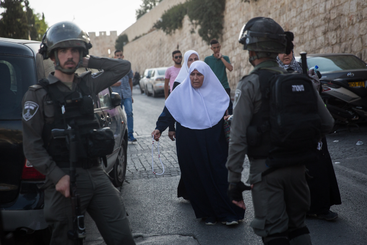 Muslim women pass by Israeli Border Police officers as they leaves Lion's Gate in Jerusalem's Old City, July 27, 2017. (Hadas Parush/Flash90)