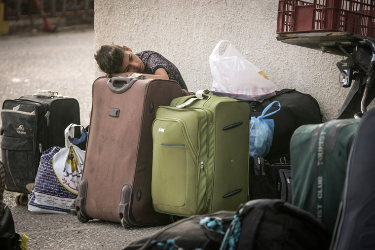 A Palestinian boy rests his head on his family's suitcases as he waits to pass through the Rafah border crossing into Egypt. Most of the Palestinians leaving Gaza through Egypt do so in order to reach third-country destinations. August 16, 2017. (Abed Rahim Khatib/Flash90)