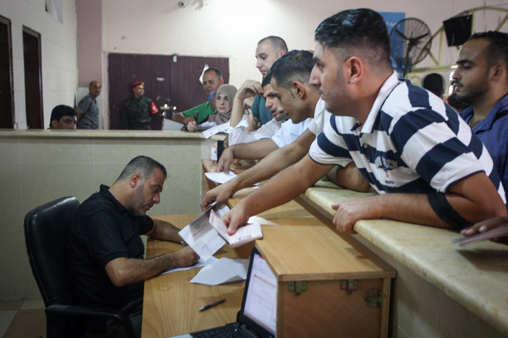 Palestinians wait to give their travel documents to a Hamas official at the Rafah border crossing during one of the rare days when it has been open for travel since Hamas took control of Gaza 10 years ago, August 16, 2017. (Abed Rahim Khatib/Flash90)