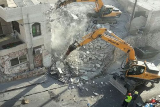 An Israeli bulldozer demolishes homes in the East Jerusalem neighborhood of Issawiya, August 15, 2017.