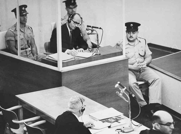 Adolf Eichmann takes notes during his trial in Jerusalem. (GPO)