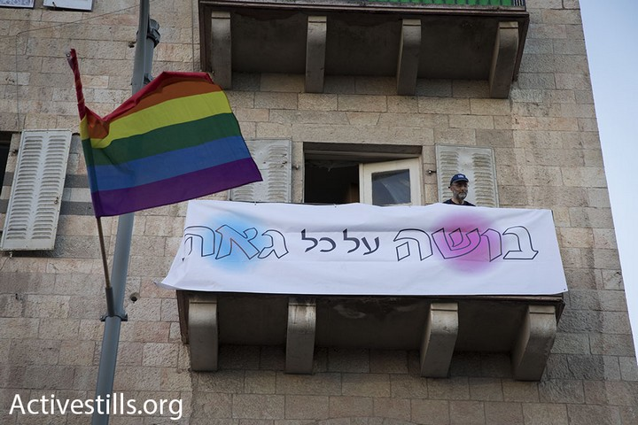 A man with a sign reading 'Shame on all those who are proud' looks on at the annual Jerusalem pride march, August 3, 2017. (Activestills.org)