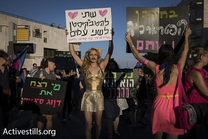 A participant in the Jerusalem pride parade holds up a sign in solidarity with LGBTQ Palestinians, Jerusalem, August 3, 2017. (Activestills.org)