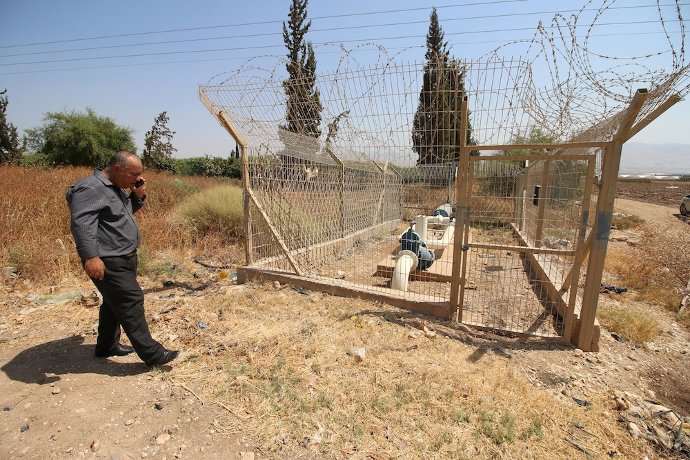 A Palestinian man walks beside one of the fenced Israeli water systems in Ein Al Beida. (Ahmad Al Bazz/Activestills.org)