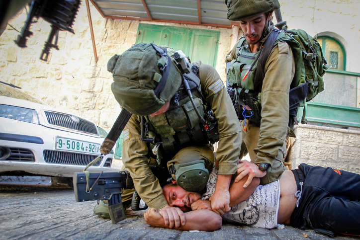 Israeli soldiers detain a Palestinian man following a raid in the West Bank city of Hebron September 20, 2016. (Wisam Hashlamoun/Flash90)