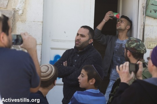 Israeli settlers surround well-known activist Issa Amro in Hebron during a tour of anti-occupation Israeli group Breaking the Silence. Amro regularly speaks to Israeli and international groups visiting Hebron to see reality in the segregated city. (Oren Ziv/Activestills.org)