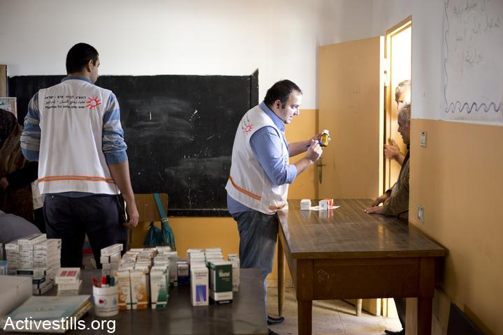 Physician for Human Rights volunteers hand out medication from a mobile clinic in the West Bank. (Oren Ziv/Activestills.org)
