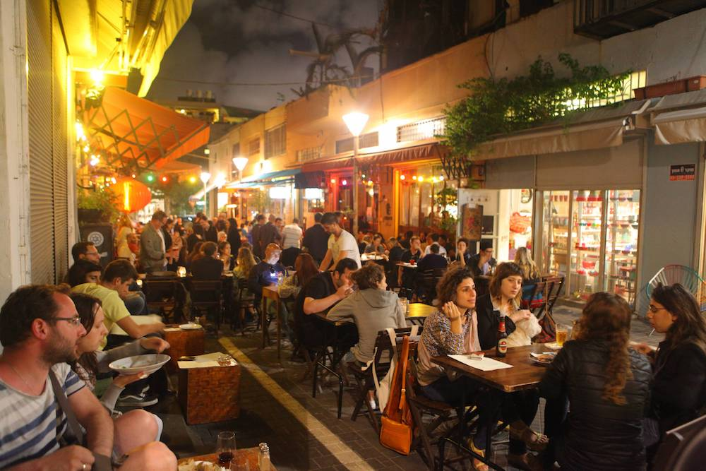 Jewish Israelis sit at a popular bar in Jaffa's rapidly gentrifying flea market area. 'People simply do not know what is happening to their neighbors. They live in completely different worlds.' (Flash90)