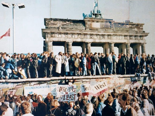 Germans celebrate the fall of the Berlin Wall at Brandenburg Gate, Berlin, 1989. (Unknown photographer)