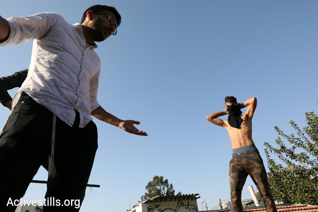 A Palestinian and settler face off on the roof of the Shamanseh family home, during a protest against their eviction, Sheikh Jarrah, East Jerusalem, September 8, 2017. (Oren Ziv/Activestills.org)