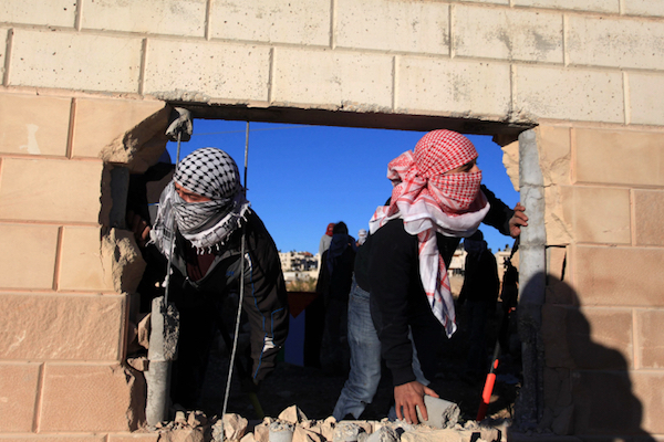Palestinians break through a section of the separation wall in the West bank city of Bir Nabala, between Jerusalem and Ramallah. (Flash90)