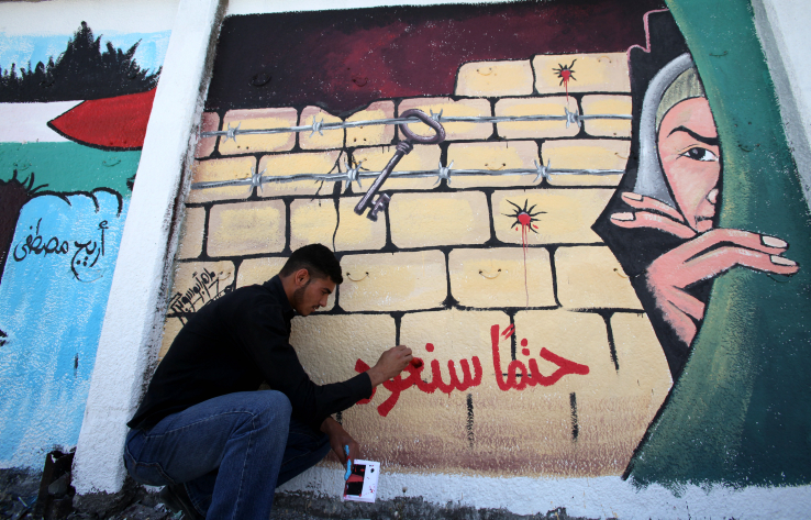 A Palestinian artist puts the final touches on a graffiti on a wall in Gaza City, May 8, 2010. The phrase is Arabic reads 'we will definitely come back.' (Wissam Nassar/Flash90)