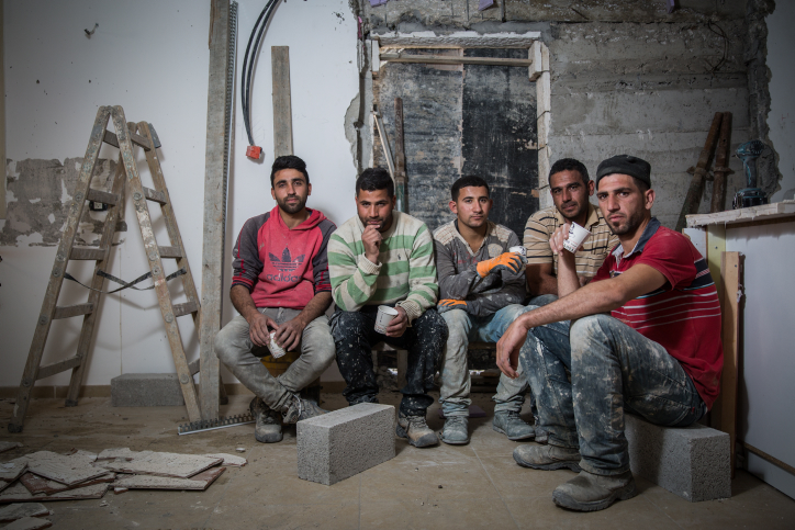 Palestinian construction workers from the village of Abadiya pose for a portrait in a house under renovation in the Israeli settlement of Alon, in the West Bank, February 16, 2016. (Hadas Parush/Flash90)