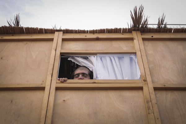 Illustrative photo of a Jewish Israeli man inside a sukkah, a temporary structure, during the Jewish holiday of Sukkot. (Flash90)