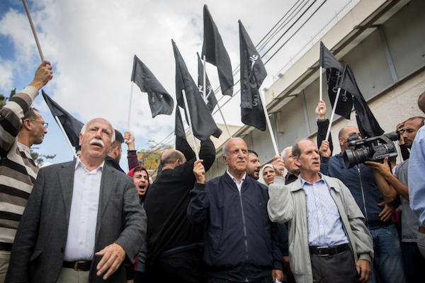 Palestinian men carry black flags at a protest marking 100 years since the Balfour Declaration outside the British Consulate in East Jerusalem, November 2, 2017. (Yonatan Sindel/Flash90)