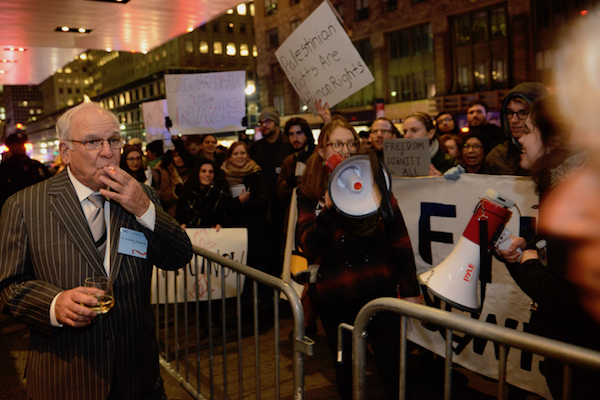 IfNotNow protesters demonstrating at the Zionist Organization of America gala as an attendee of the event looks on, New York, November 12, 2017. (Gili Getz)