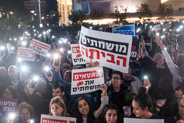 Israelis holding signs and shout slogans during a protest against the corruption of the government in Tel Aviv on December 9, 2017. (Tomer Neuberg/Flash90)