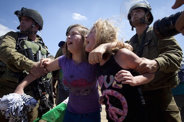 Israel soldiers grab Ahed Tamimi and a relative as she is being arrested at the entrance to Nabi Saleh's water spring, during the weekly protest against the occupation in the West Bank village, August 24, 2012. (Activestills)
