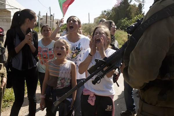 Palestinian children and women face Israeli soldiers during the weekly protest against the occupation in the west Bank village of Nabi Saleh, April 20, 2012. (Activestills)