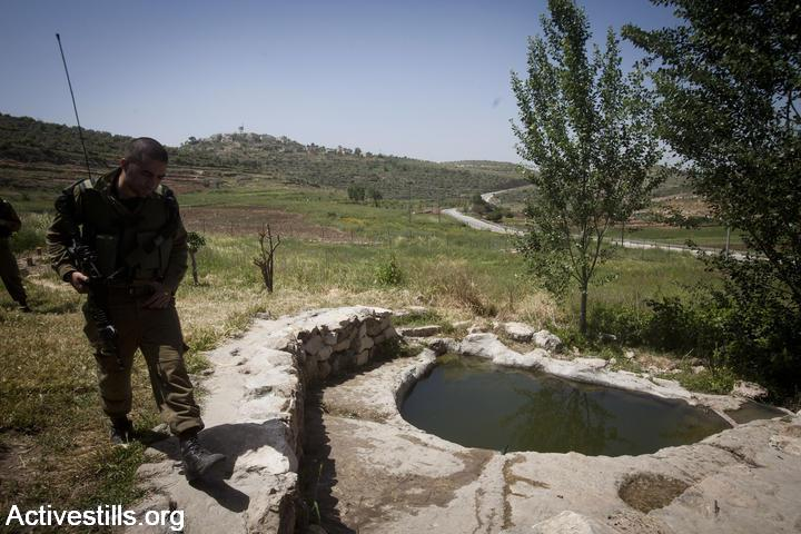 An Israeli soldier patrols at the spring in Nabi Saleh, after it was taken over by settlers, April 22, 2012. (Oren Ziv/Activestills.org)