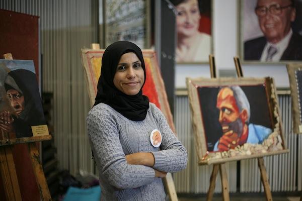 Artist Tahreer Alzbede stands next to her portrait of Yacoub Abu Al-Qian at the 'Demolition Order' exhibition at Ben Gurion University, December 10th, 2017. (Maya Avis)