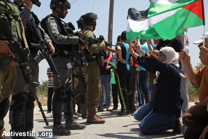 Palestinian protesters sit in front of Israeli soldiers during a protest against the occupation and in solidarity with the Palestinian prisoners hunger strike, in the West Bank village of Nabi Saleh, May 12, 2017. (Haidi Motola/Activestills.org)