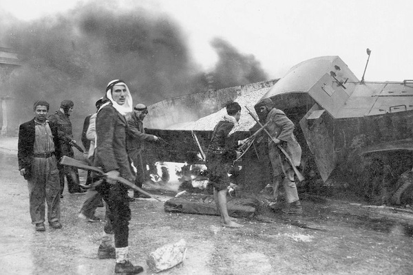 Palestinian irregulars near a burnt armored Haganah supply truck, the road to Jerusalem during the 1948 war. (Palmach Archive)