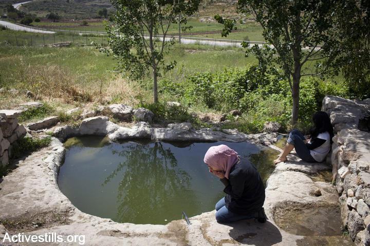 Palestinian, Israeli and international women enjoy a picnic near a water spring in Nabi Saleh, April 22, 2012. (Oren Ziv/Activestills.org)