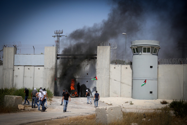 Palestinian youths burn tires next to Israel's separation wall in Qalandiya, in between Jerusalem and Ramallah, West Bank. (Flash90)