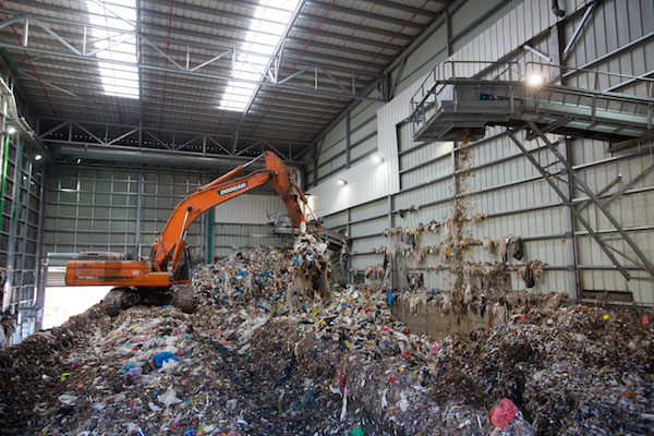 A bulldozer lift garbage at the Greenet recycling plant in Atarot industrial zone, near Qalandiya, on June 16, 2015. (Sindel/Flash90)