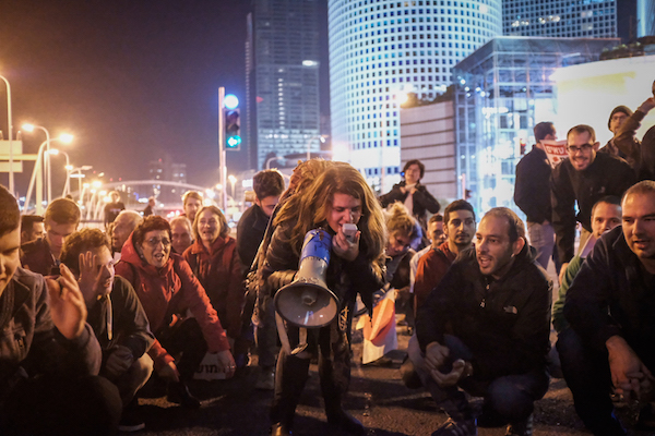 Israelis block a road during a protest against the corruption of the government in Tel Aviv on December 9, 2017. (Tomer Neuberg/Flash90)