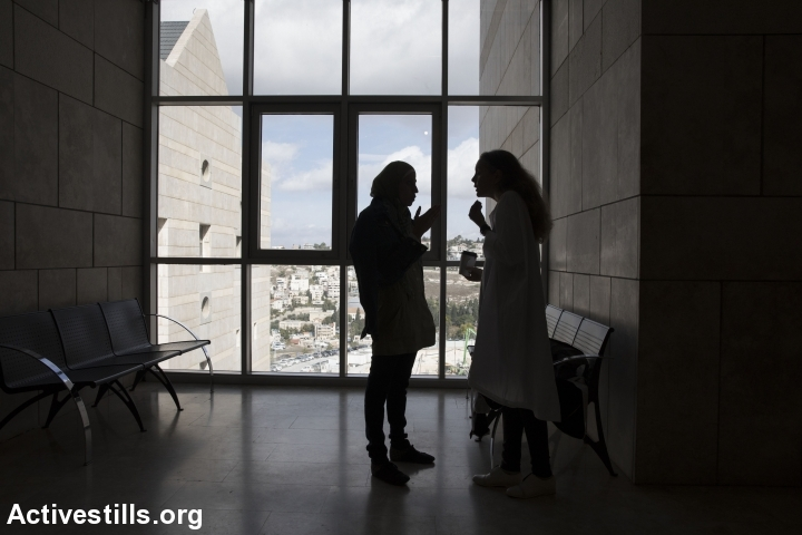 Dareen Tatour speaks with her attorney, Gaby Lasky, outside the Haifa courtroom where her trial was taking place. (Oren Ziv/Activestills.org)