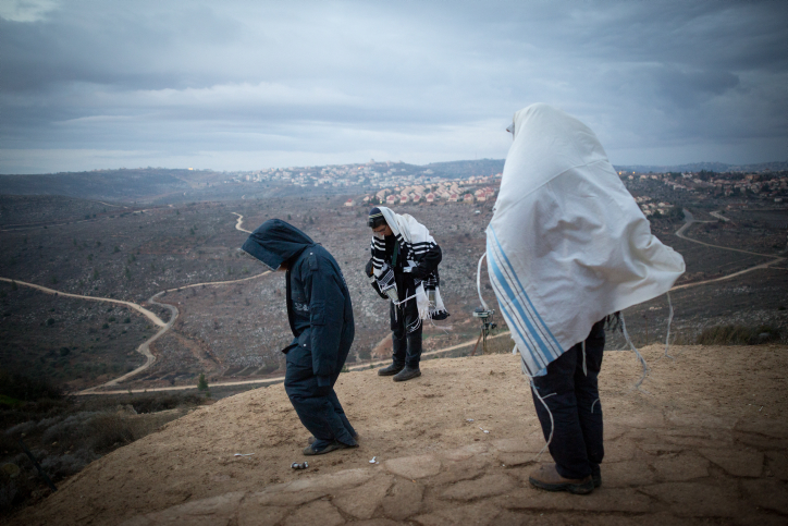 Jewish men pray early in the morning on the hill overlooking Ofra in the Jewish settlement of Amona in the West Bank, December 18, 2016. (Miriam Alster/Flash90)