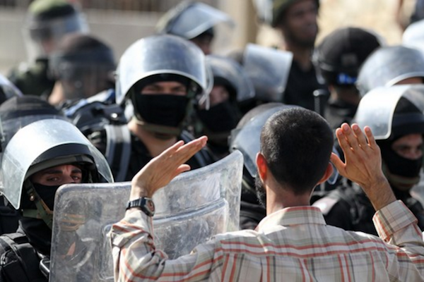 A Palestinian citizen stands before Israeli police forces during a demonstration in the city of Umm al-Fahm, October 2010. (Nati Shohat/Flash90)
