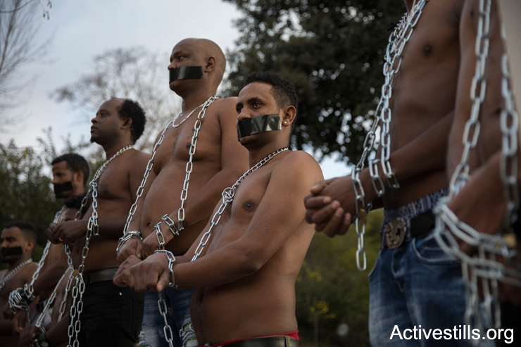 Eritrean asylum seekers stage a mock slave auction outside the Knesset to protest Israel's plans to deport tens of thousands of Sudanese and Eritrean asylum seekers, January 17, 2018, Jerusalem. (Oren Ziv/Activestills.org)