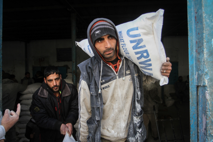 Palestinians in the southern Gaza city of Rafah receive monthly food rations from an UNRWA distribution center, January 23, 2017. (Abed Rahim Khatib/ Flash90)