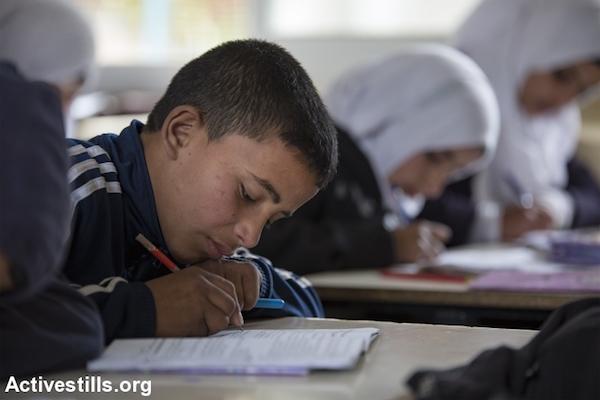 Students sit in a classroom at school in the Jahalin Bedouin community of Khan Al-Ahmar, West Bank, February 22, 2017. (Faiz Abu Rmeleh/Activestills.org)