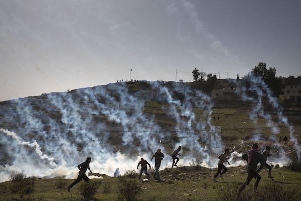 Demonstrators flee a barrage of tear gas fired by Israeli soldiers in Nabi Saleh. January 13, 2018. (Oren Ziv/Activestills.org)