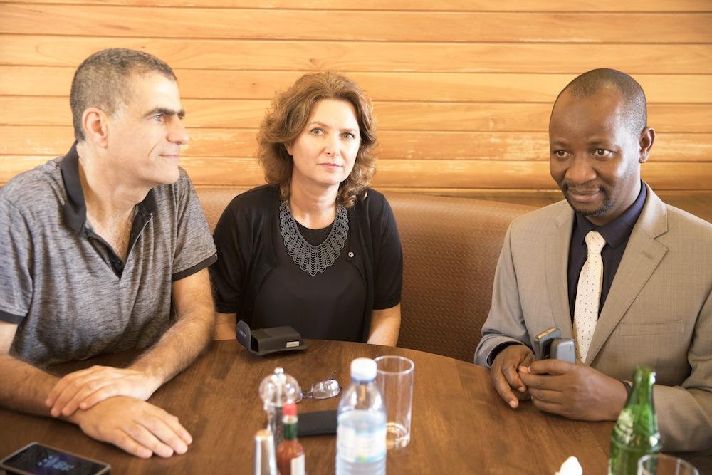 Meretz MKs Mossi Raz (left) and Michal Rozin (center) meet with Ugandan lawmaker Ssemujju Ibrahim Nganda in a cafe in Kampala, Uganda. (Oren Ziv/Activestills.org)