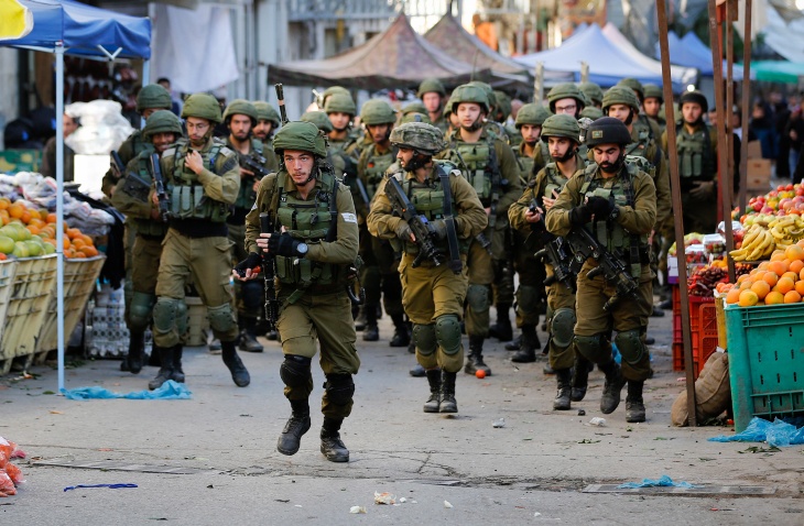 Israeli forces walk down a street during clashes with Palestinian demonstrators in Hebron in the Israeli-occupied West Bank, December 9, 2017. (Wisam Hashlamoun/Flash90)