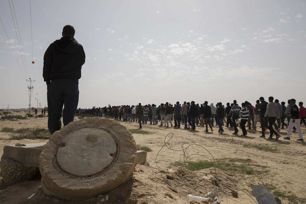 Hundreds of Eritrean and Sudanese asylum seekers march out of Israel's desert detention facility for asylum seekers, Holot, in protest of the deportation plan, February 22, 2018. (Oren Ziv/Activestills.org)
