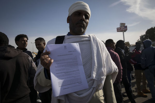 An asylum seeker holds the deportation notice issued to him by the Interior Ministry. February 4, 2018. (Oren Ziv/Activestills.org)